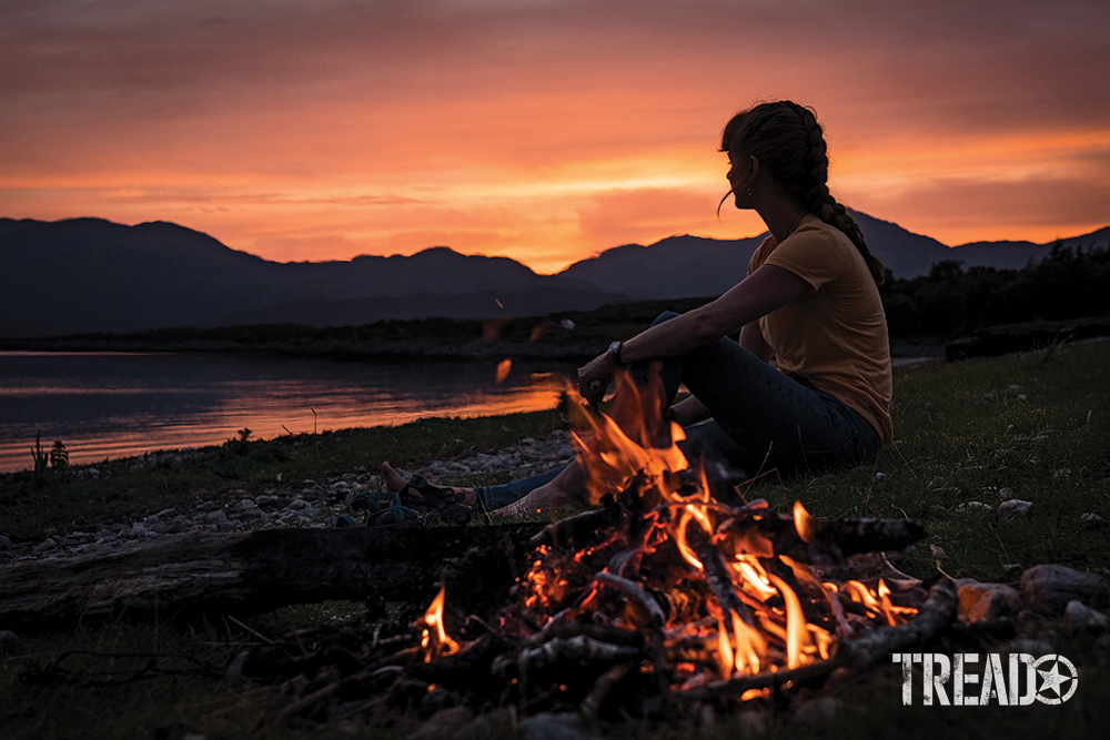 Pink and orange skies give way to a hilly backdrop while a woman sits next to a campfire on a beach.