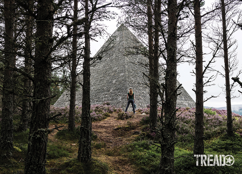 Scotland's secret pyramid might not be of an Egyptian caliber, but it strikes a pose behind tall trees with a woman standing in front of it.