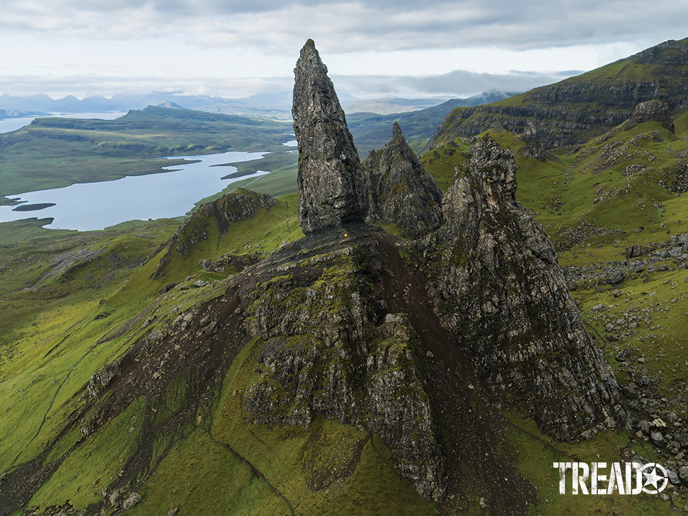 The Old Man of Storr rock formation soars over lush, green Scottish countryside and waterways.