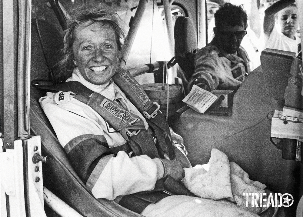 Black and white photo of smiling Sue Mead as she sat as co-driver, next to legendary racer Rod Hall.