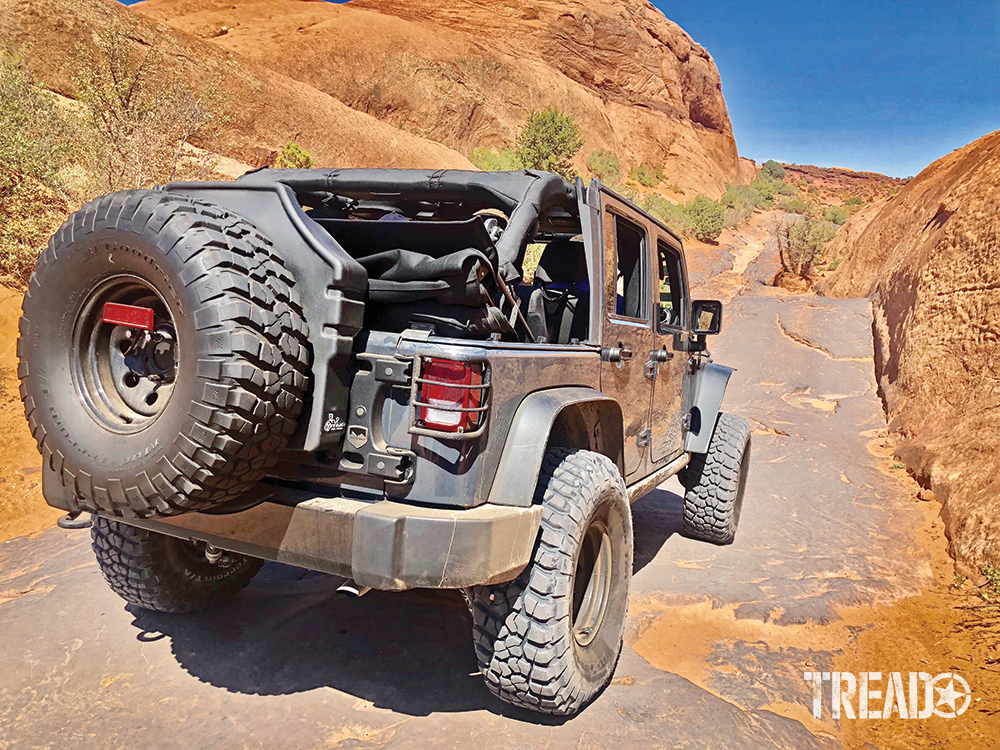 A customized gray Jeep with Titan spare tire tank is driving over Moab's Hell's Revenge Trail.