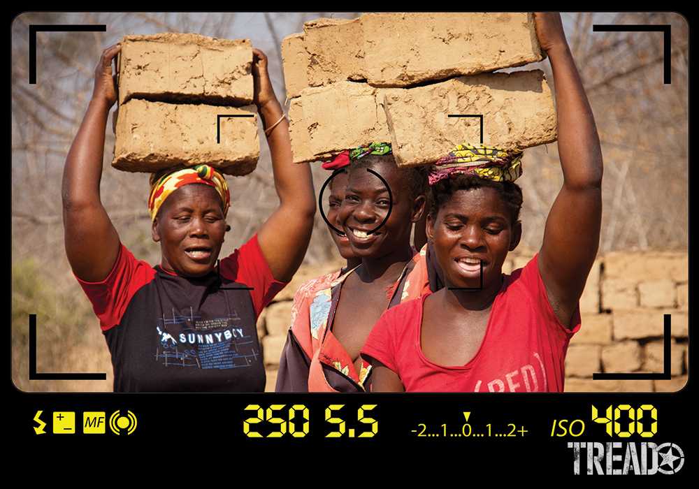 The ladies of a small village, near Lake Kariba, Zambia, have dark skin and wear brightly colored clothing as they carry mud bricks on their head.