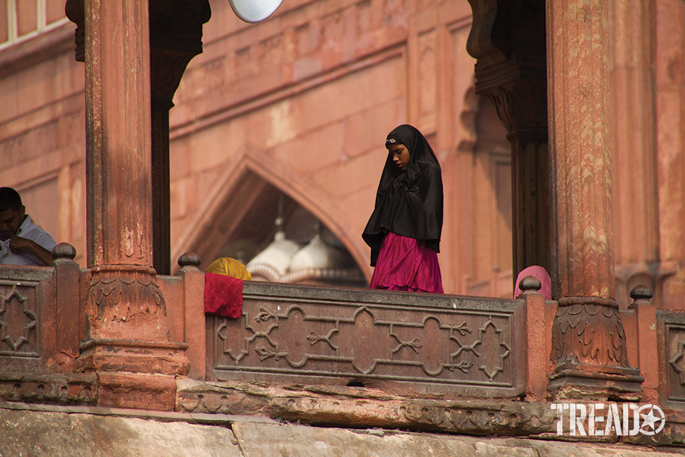 A woman in a black covering with dark pink shirt prays outside the Jama Masjid Mosque in Delhi, India.