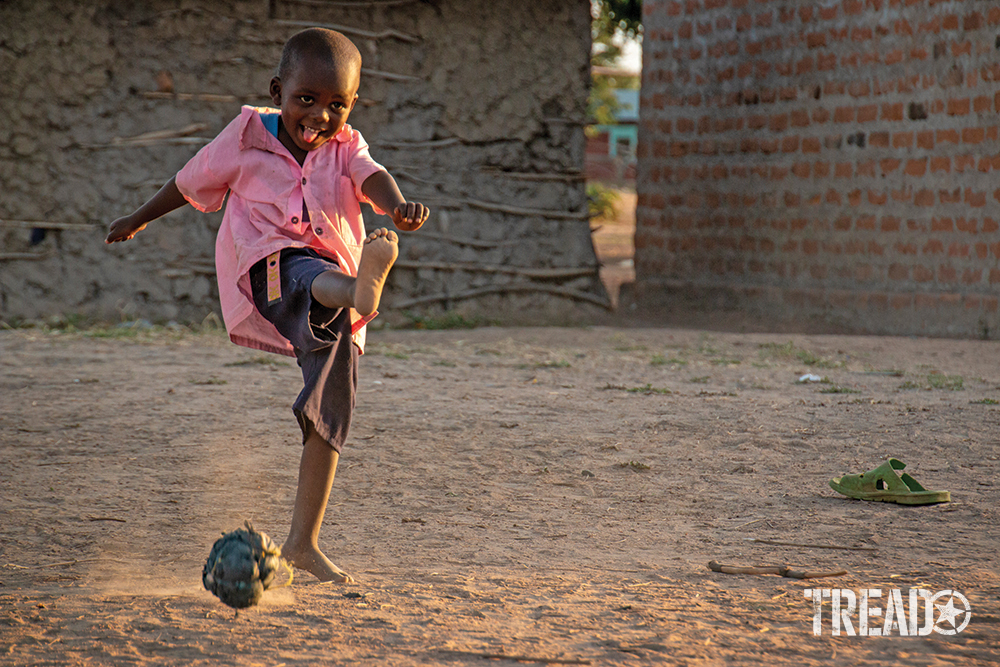 A Kenyan child in pink short and shorts plays soccer with plastic and twine ball.