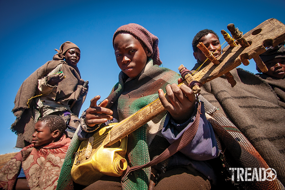 Dark-skinned children playing water can drums and guitars crafted from scrap lumber and corn oil jugs.