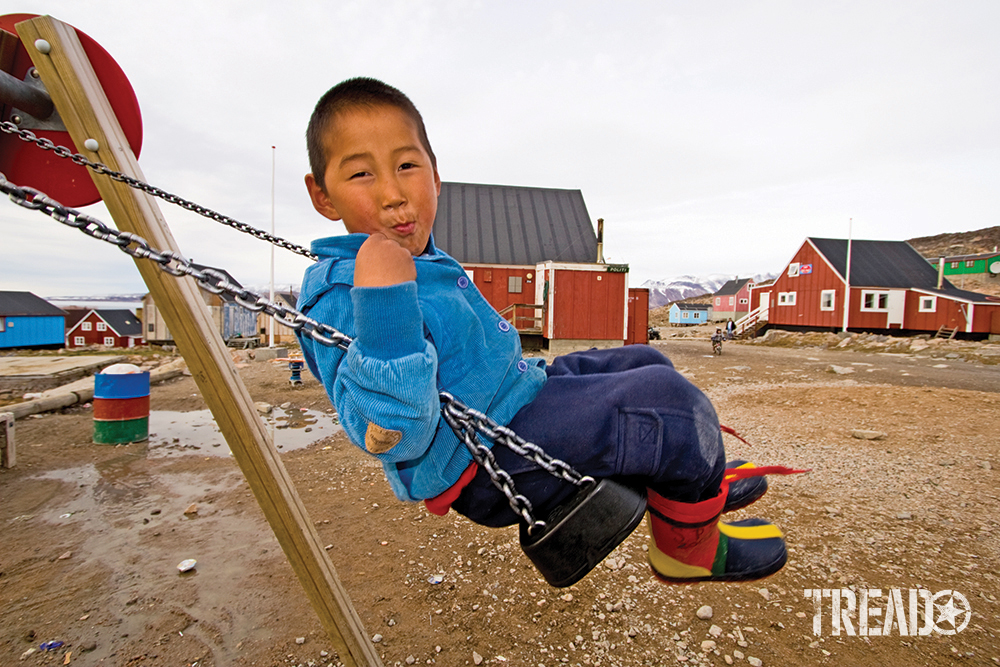 Inuit boy swinging on swing set wearing clue jacket and colorful boots smirking at camera.