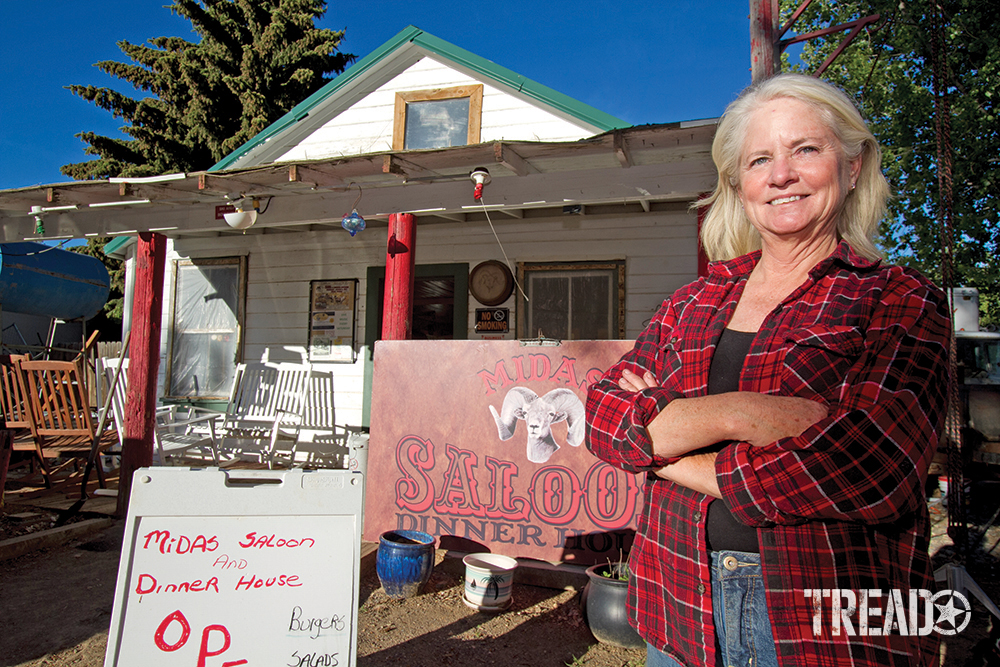 The proprietor, a woman wearing red flannel shirt, standing in front of Midas Bighorn Saloon, Midas, Nevada