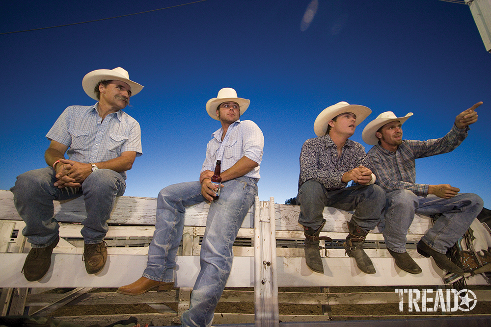 A group of brothers, rodeo riders, sit on fence with beers in hand, one pointing to the action.