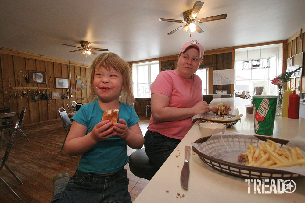 The café in Lone, with proprietor and daughter, eating french fries sitting on stools in wood-paneled interior with ceiling fans.