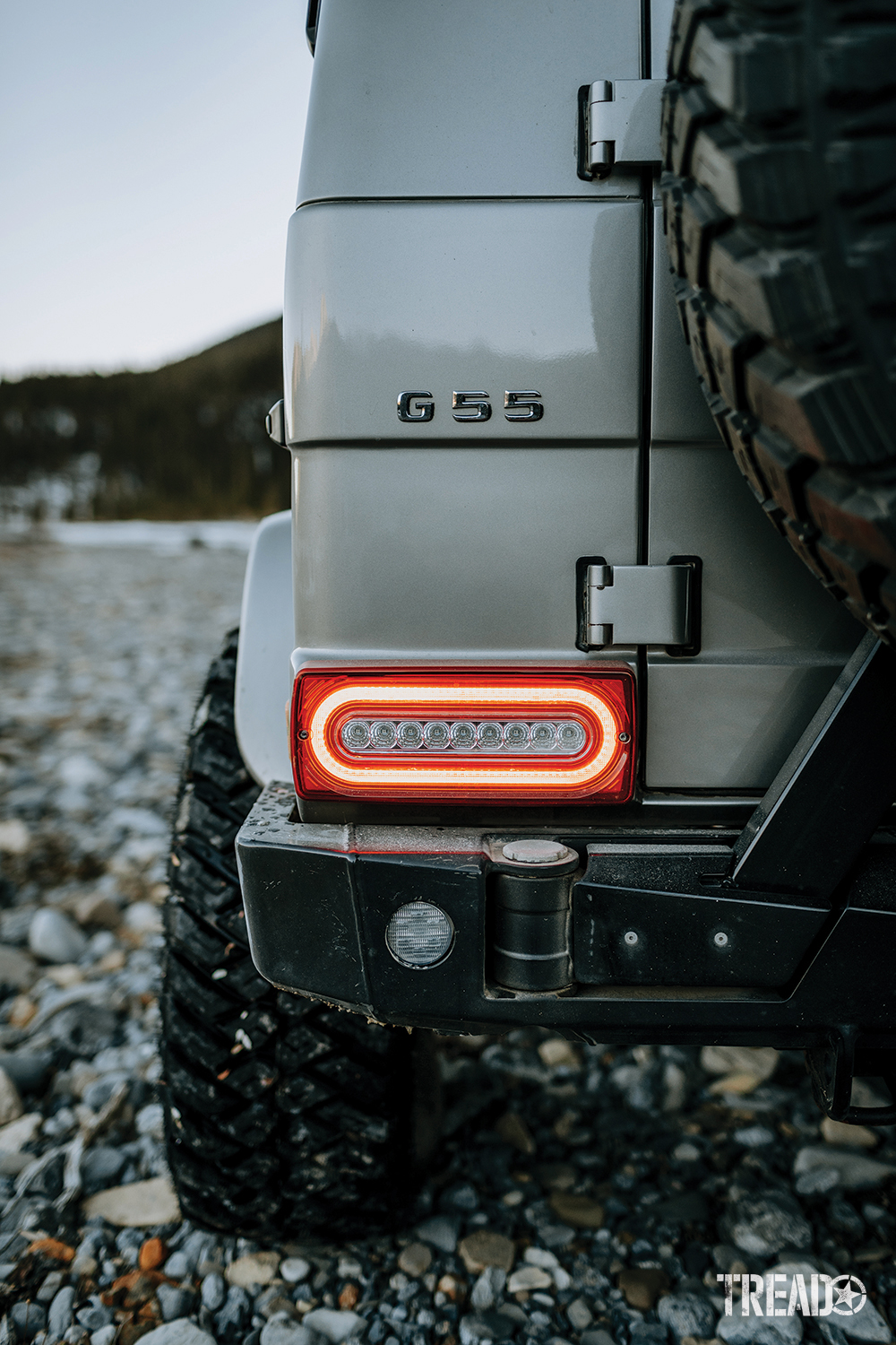 The black G-Wagen AFN rear bumper fits the silver G-Wagen's body lines and sits below a brightly lit brake light.