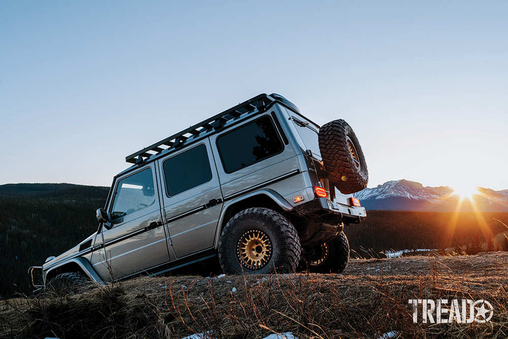 The silver 2004 Mercedes AMG G55 G-Wagen goes downhill during sunset.