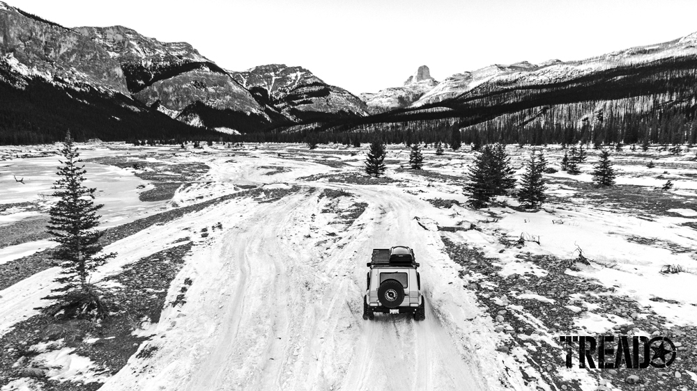 A Mercedes G-Wagen travels on a snowy covered trail, headed to the mountains.