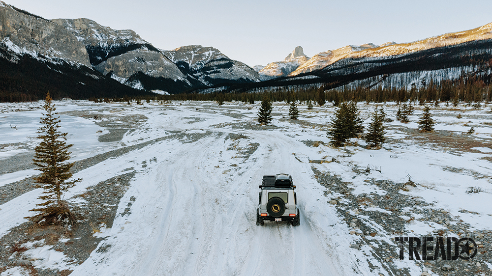 The silver luxury G-Wagen 4x4 drives on a snowy trail to nearby mountains.