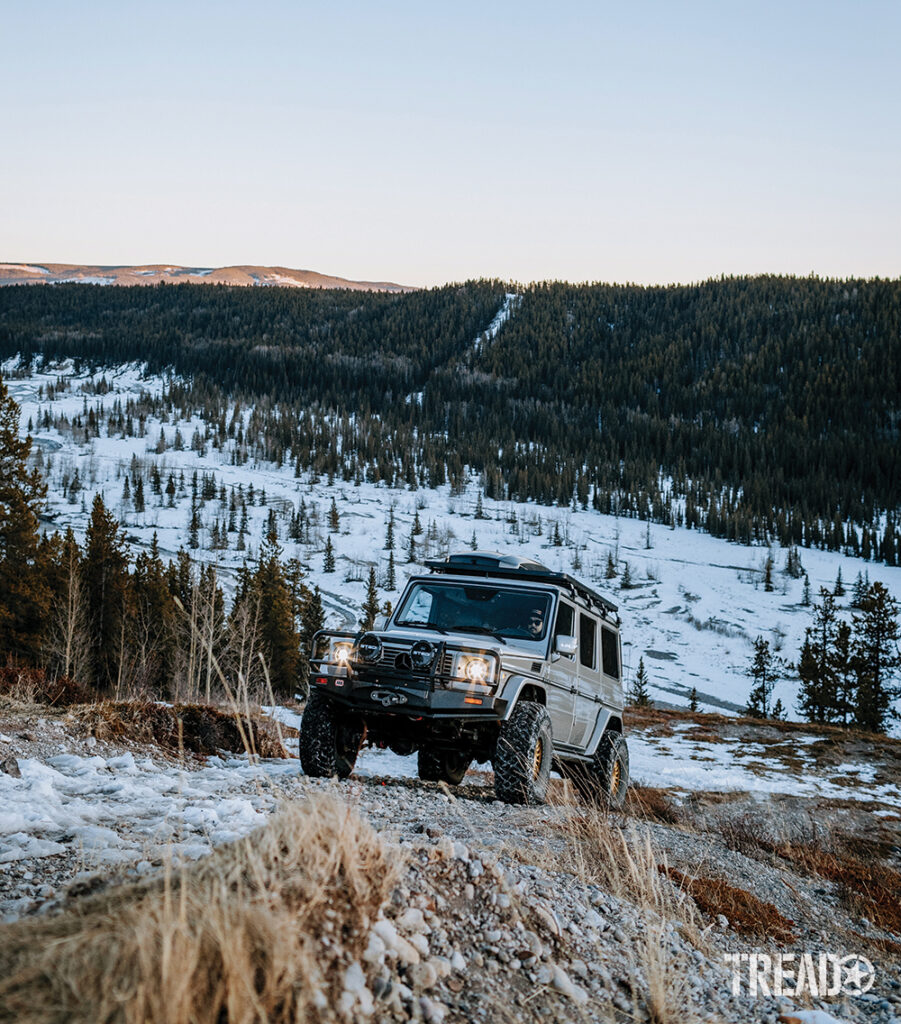 The silver Mercedes G-Wagen heads uphill on a partially snow-covered trail with hillside of pine trees behind it.