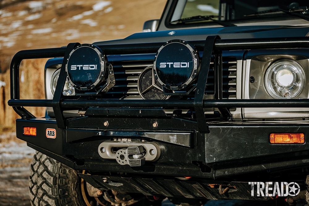 Front winch bumper, bull bar, and black-covered aux lights on silver Mercedes G-Wagen.