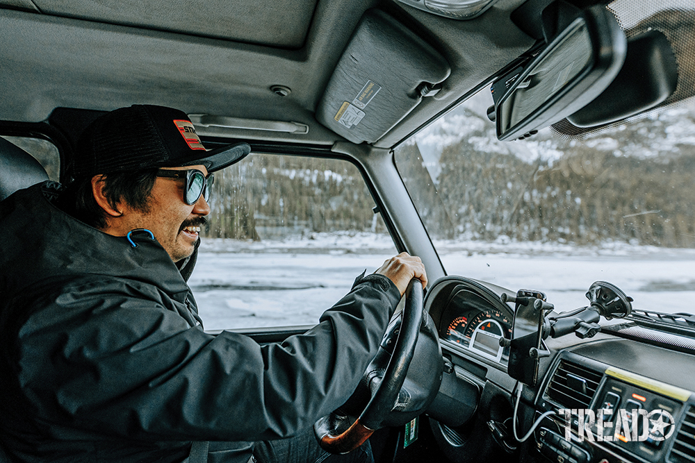 Nathan, wearing gray jacket and black hat with mustache, smiles as he drives his Mercedes G-Wagen.