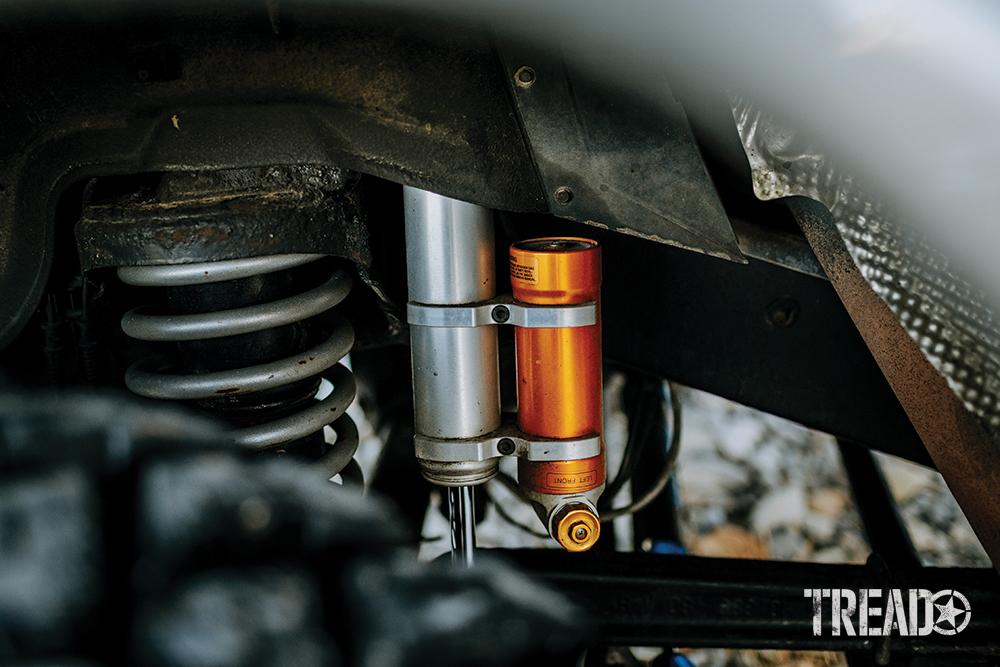 Silver and orange MEV Reservoir shocks sit behind beefy off-road tires.