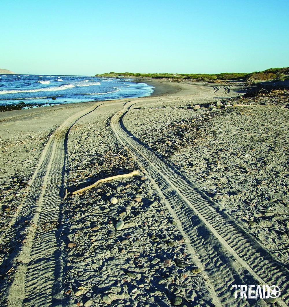 Tire tracks on soft sand tracks towards the oceanside.