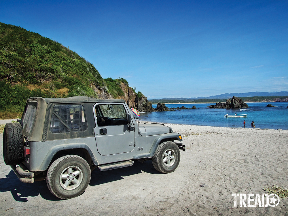 Silver two-door soft-top Jeep sitting on beach next to lush hillside.