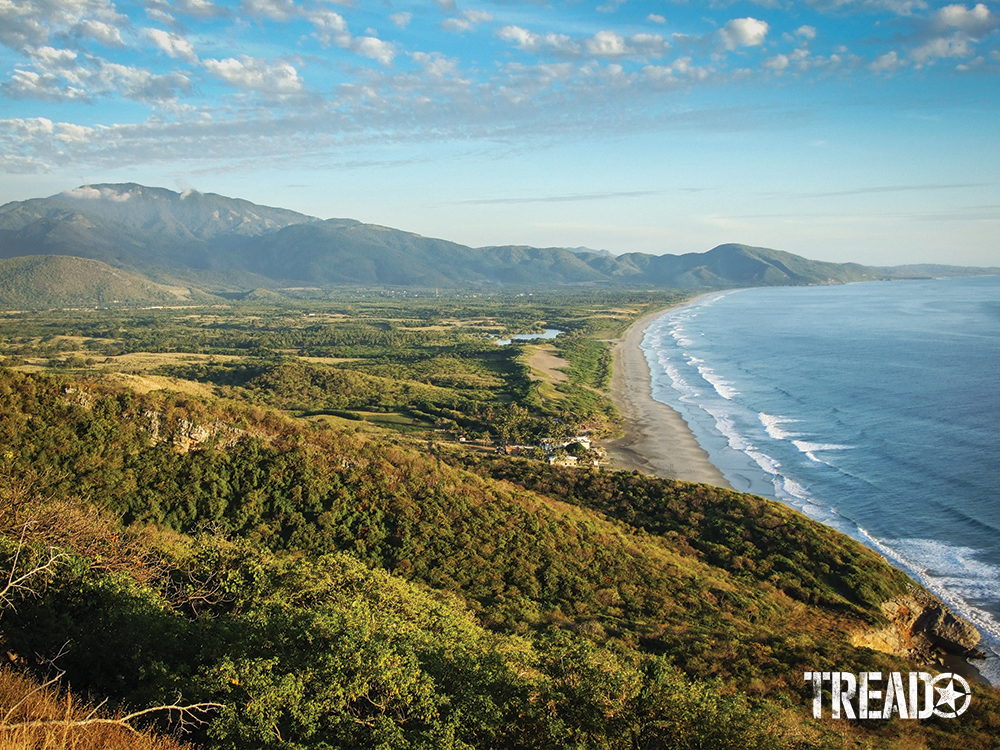 Undulating hills and green shrubs clear their way to Mexico's beaches, with waves wafting into shore.
