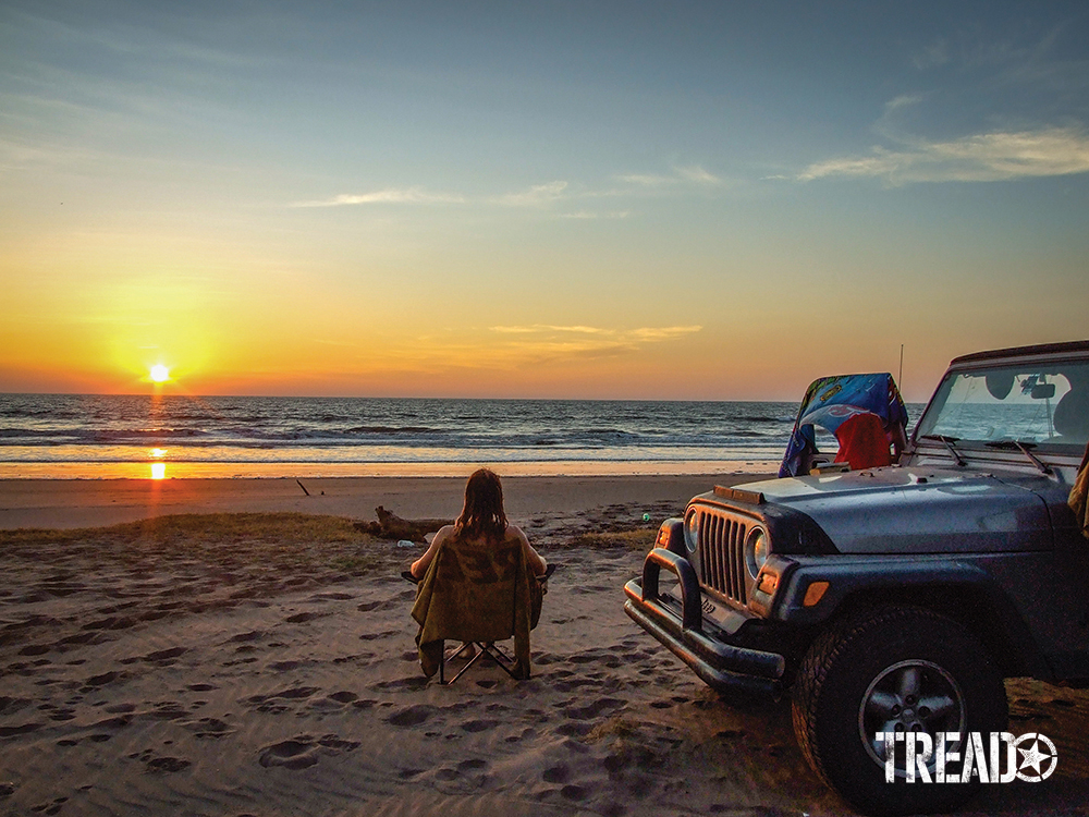 Man sitting in chair on beach watching sunset while silver Jeep is next to him.