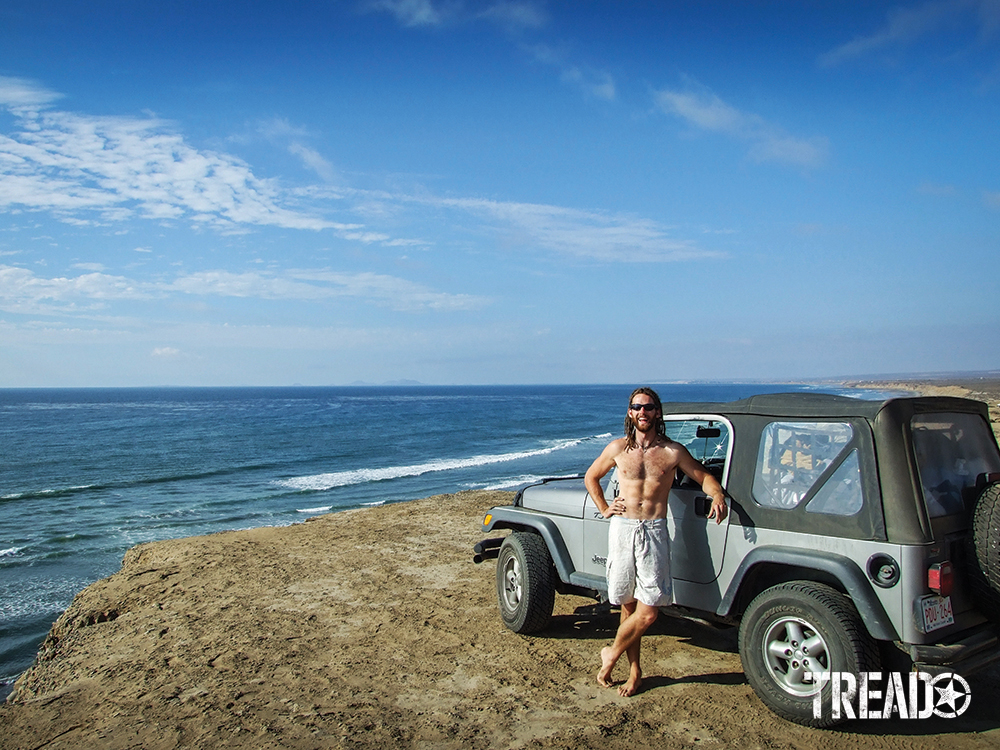 Shirtless man with white shorts standing next to silver Jeep next to ocean on beach.