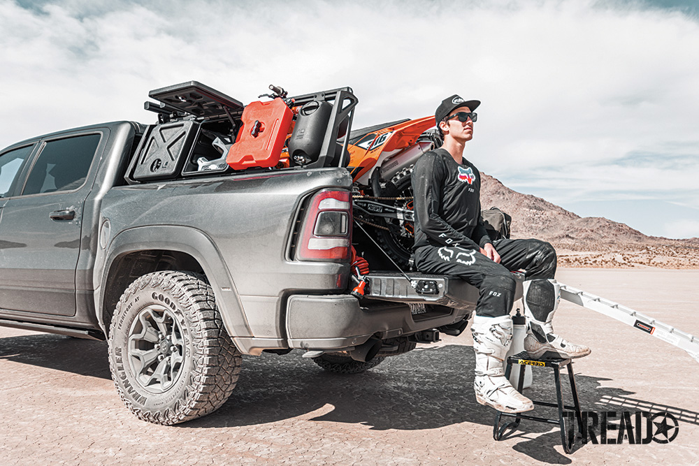 Man sits on tailgate of truck with dirt bike in back and bed rack storage holding gear shown.