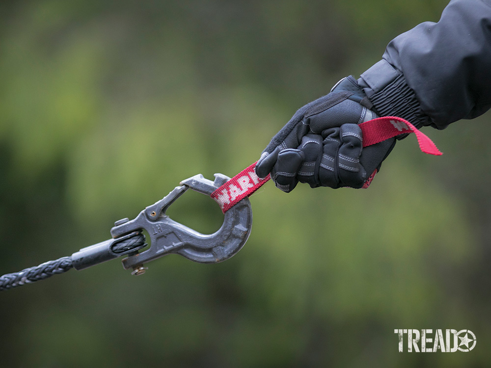 """If you're winching using a hook, always remember to """"hook up."""" The dark gray WARN Epic hook is being pulled by a red WARN safety strap. This will help the line fall toward the ground in case of rope failure."""