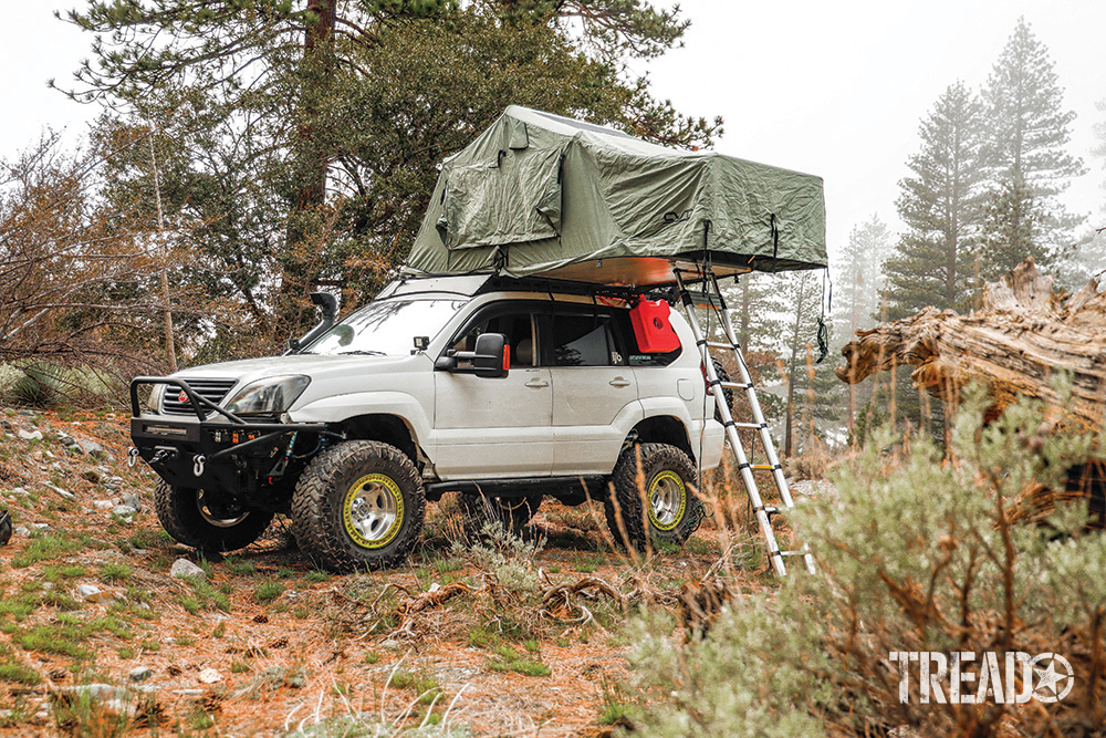 A white Off-road Lexus GX 470 has sage colored rooftop tent open with ladder deployed.