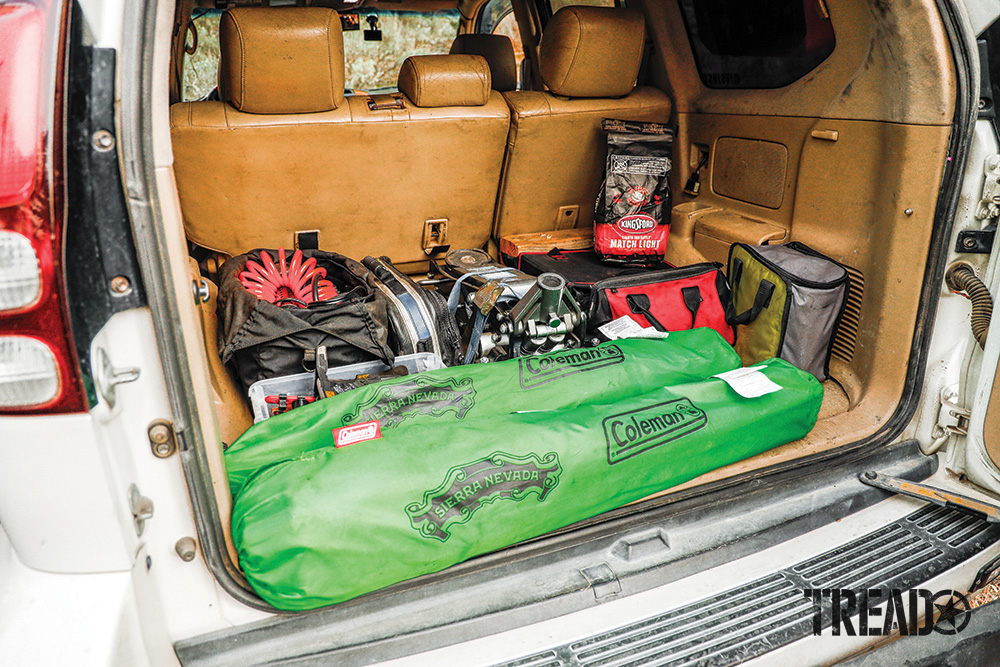 The rear cargo area reveals a medium-tan interior which is used for Brian's air compressor, Pro Eagle, recovery gear, bright green camp chairs and more.