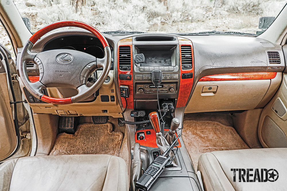 The tan, gray, and wood-accented cockpit of the of-road GX 470 is functional and simple.
