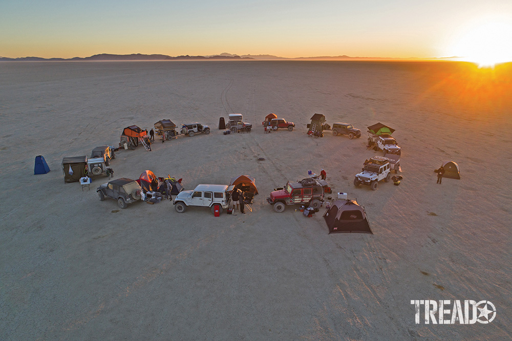 A group of customized 4x4s collect in a circle on a dried lakebed as the sun sets.