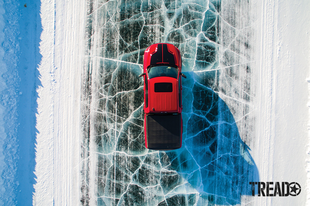 Shown in a bird's eye view, a red truck with black tonneau cover is driving on Arctic ice road.