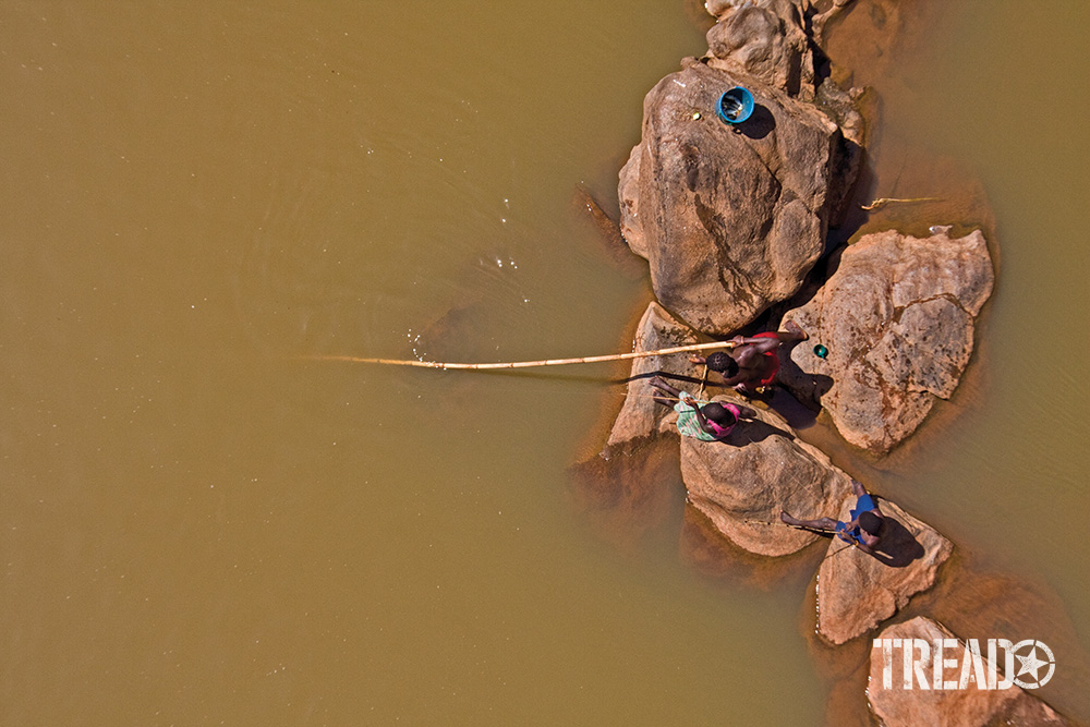 A bridge can be an excellent way to gain a stealth bird's-eye view. These teenagers were unaware of the author's presence without a buzzing drone overhead. They fished on large peach-colored rocks along a river in southern Mozambique.