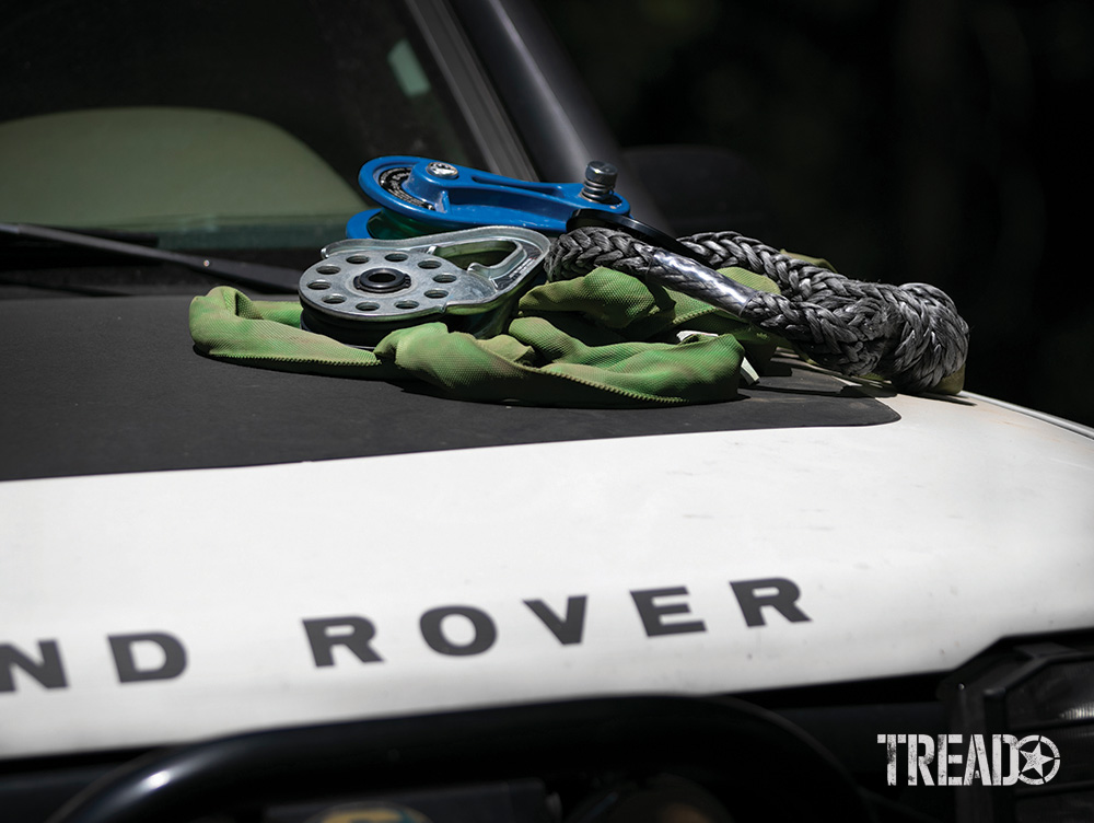 Various recovery slings, snatch blocks and soft shackles are laying on a Land Rover's hood.