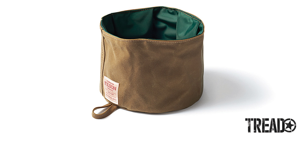 The collapsible tan and green dog bowl from Filson folds to store in a pocket or clips onto your pack with the attached hanging loop.