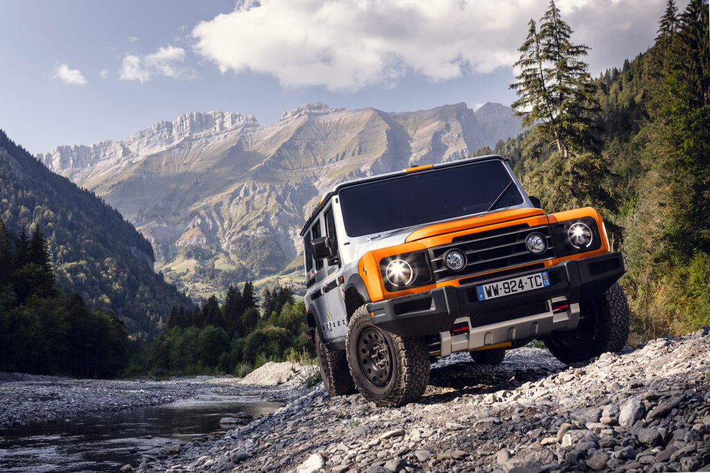 An orange and silver INEOS Grenadier prototype traverses a rocky mountain trail with mountain range behind it.