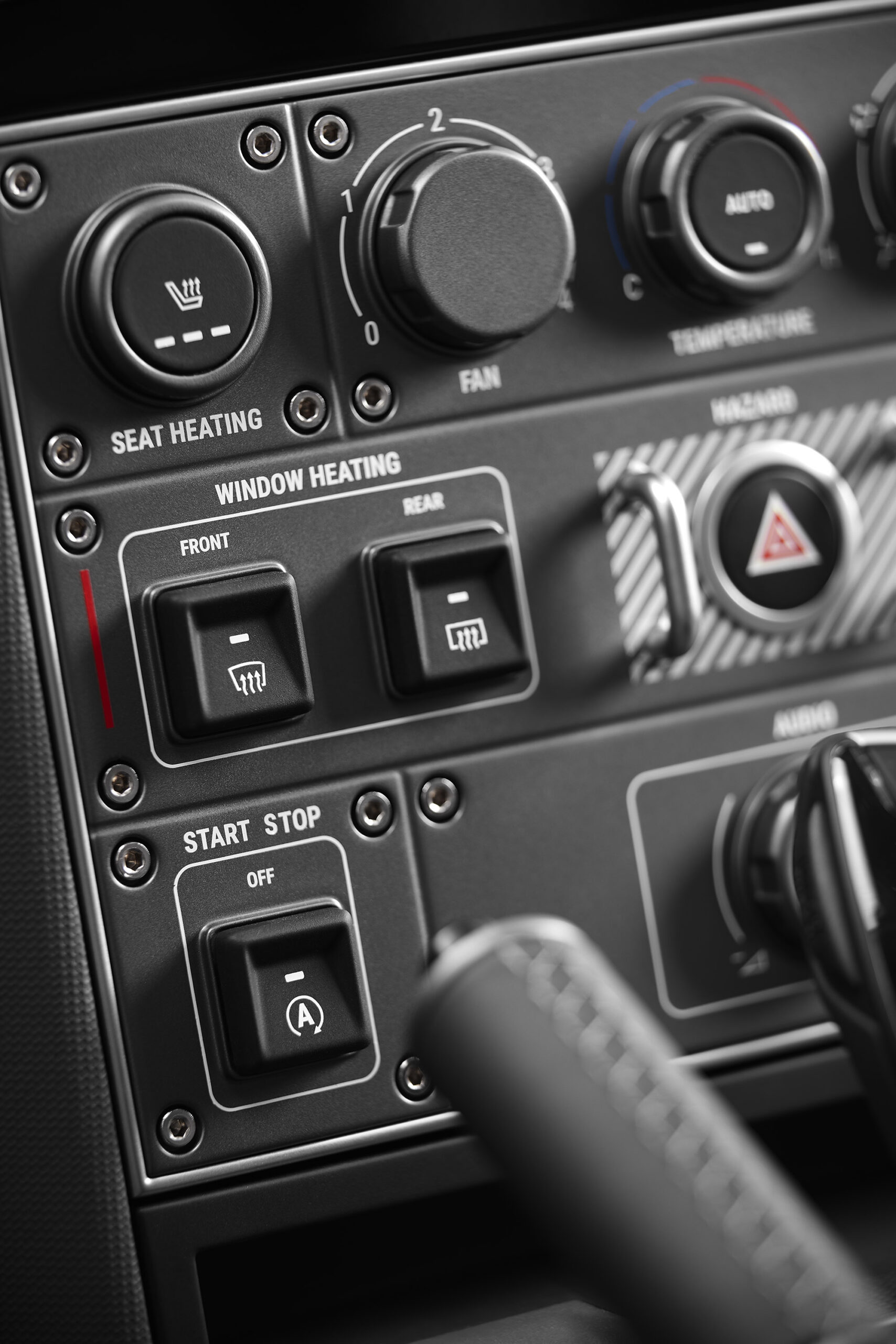 The INEOS interior includes oversized black toggle switches, rotary dials, and evenly spaced controls.