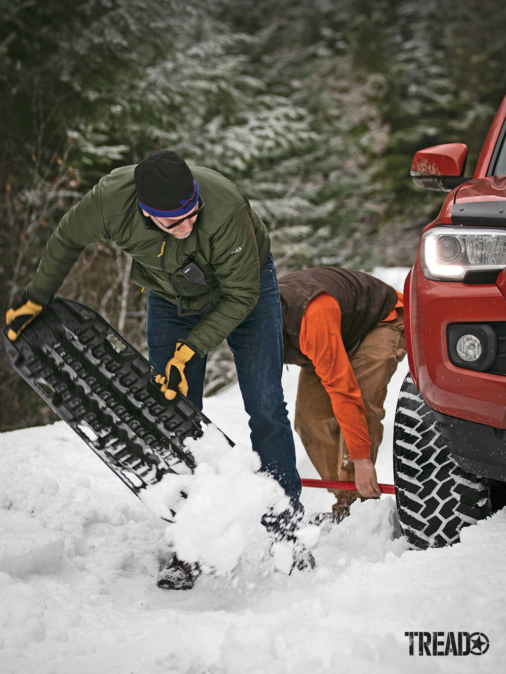Two men use a black recovery board and red shovel to dig out an orange Toyota truck in deep snow.