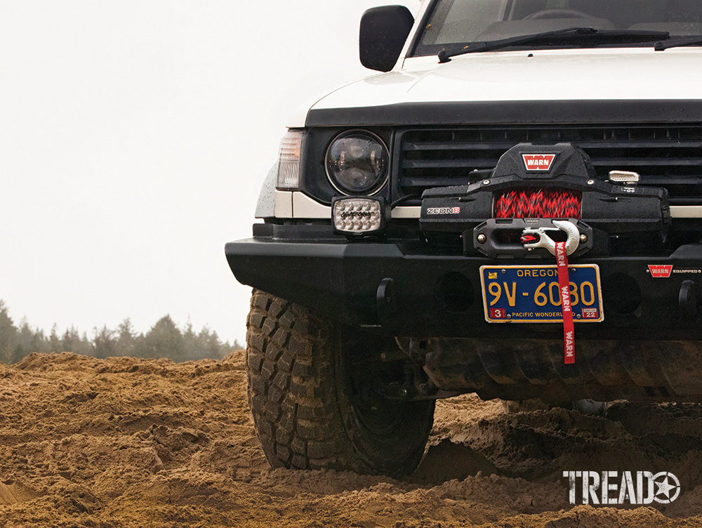 This white 1992 Mitsubishi Pajero is outfitted with a WARN winch bumper, WARN winch, red and black WARN Nightline synthetic rope, and Lightforce aux lights.