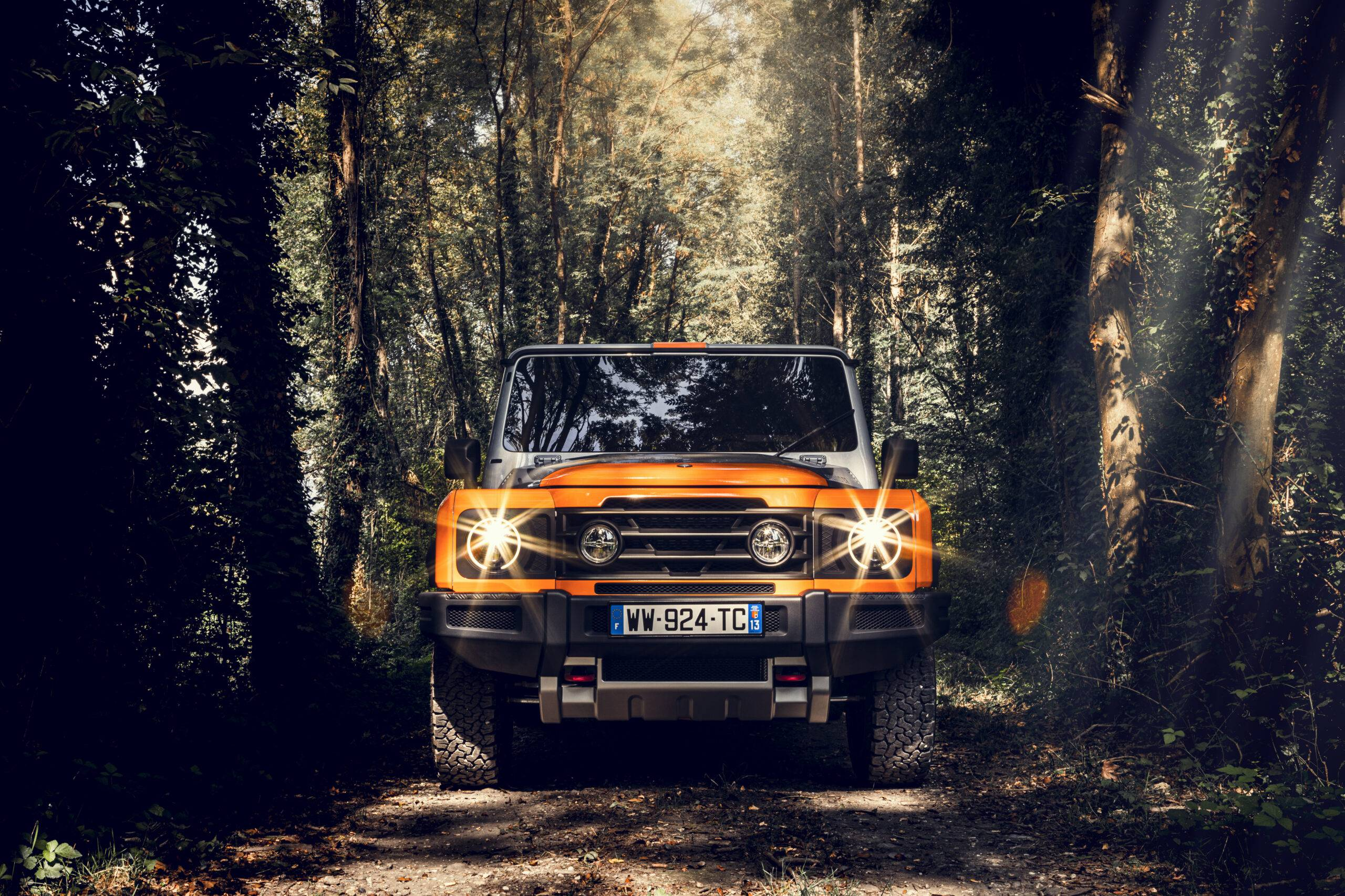 The orange and silver INEOS Grenadier's front end with lights on in a thick forest.