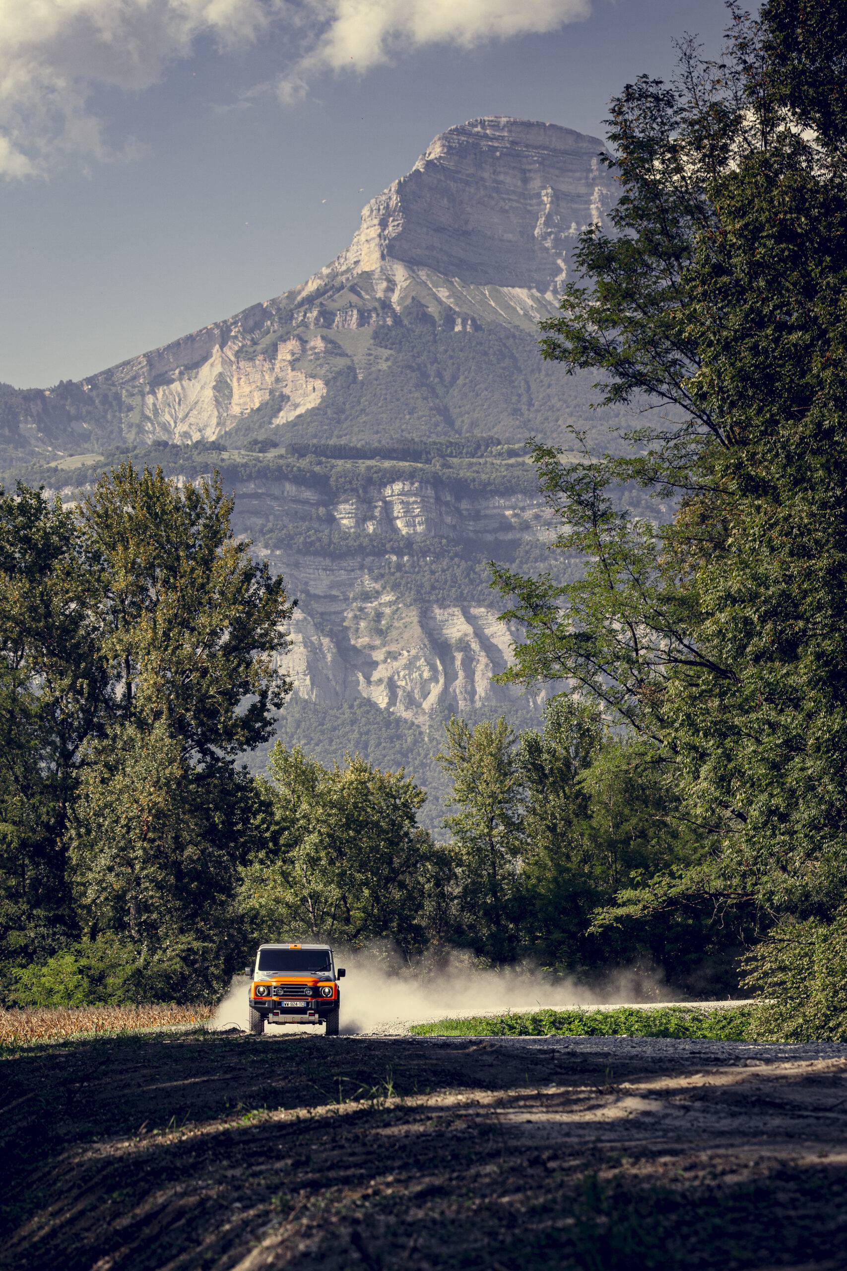 The orange and silver INEOS Grenadier drives on dirt road in front of mountains
