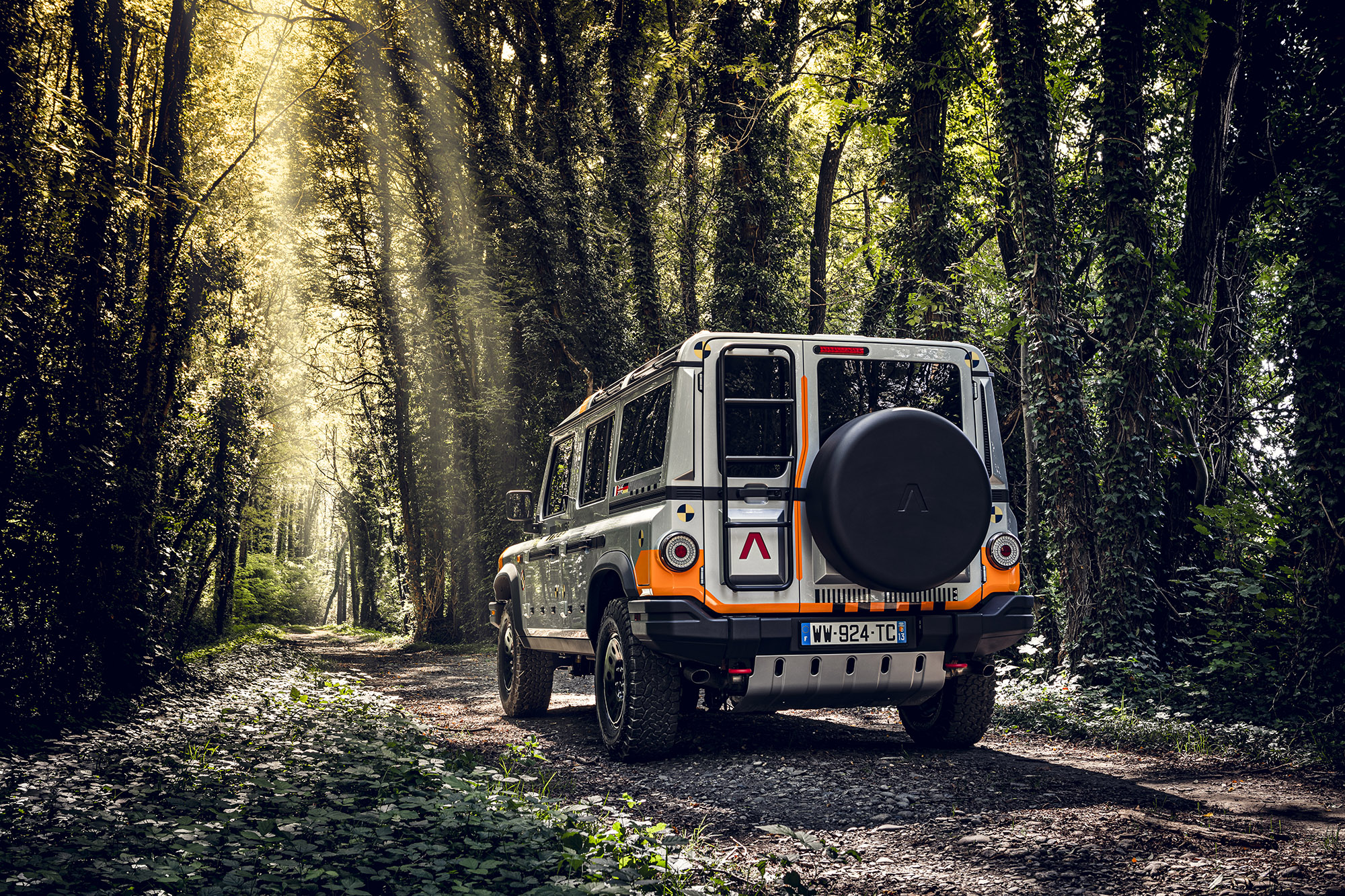 The orange and silver INEOS Grenadier prototype boasts a full-size spare, OE ladder, and beefy off-road tires.