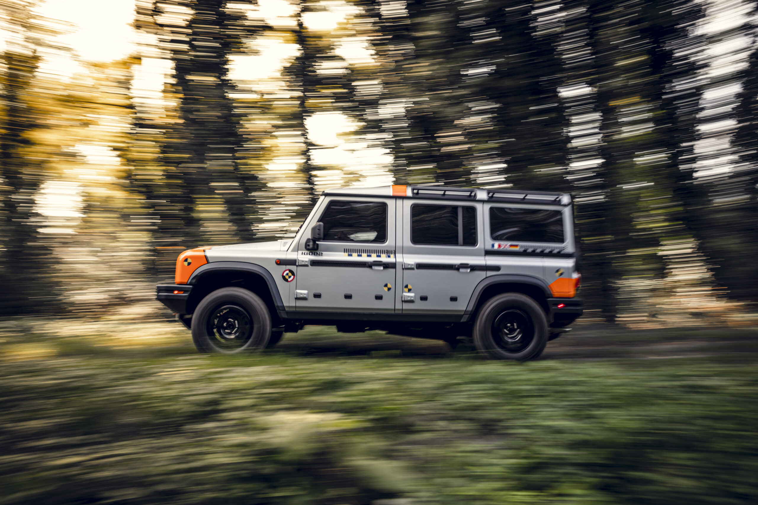 A silver INEOS Grenadier prototype drives quickly through forest roads for testing