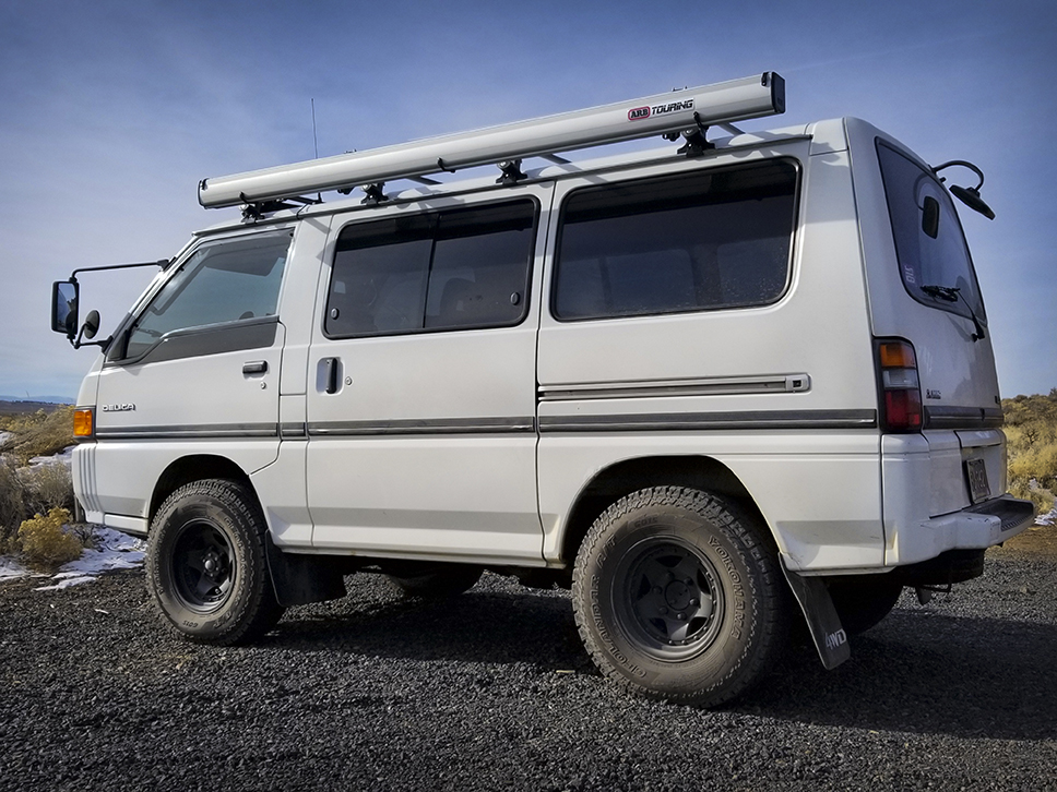 Side view of white Delica Star Wagon parked on road.