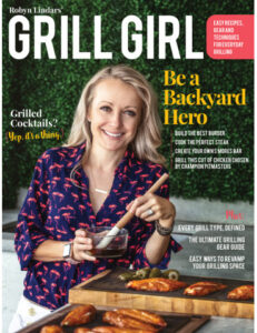 Woman holds basting brush next to grill.