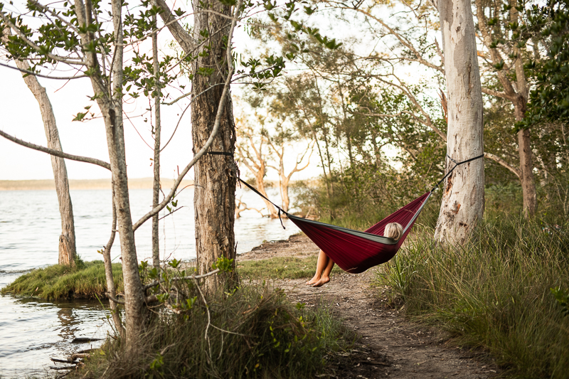 person lays in red hammock tied between two trees next to a lake