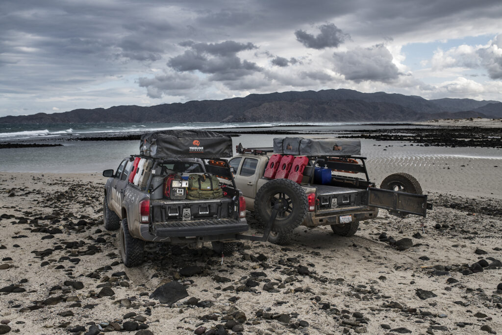 Two trucks parked on beach that have Decked drawer system.