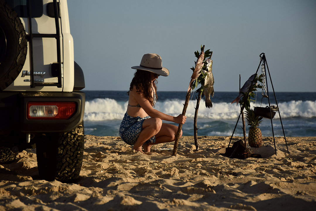 Woman cooks fish on beach next to SUV.