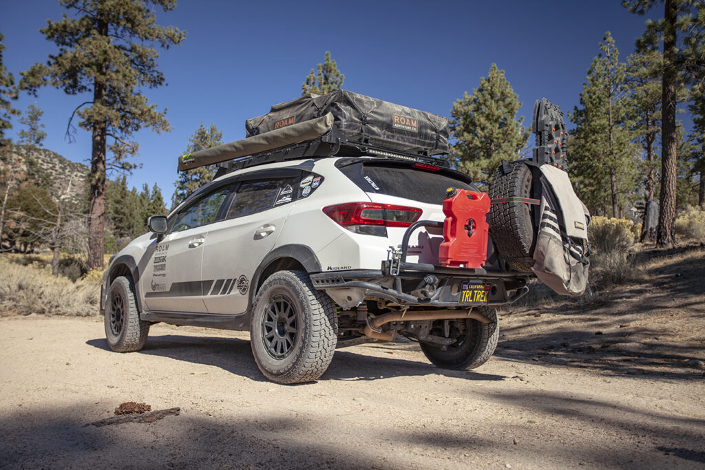 From Tread July/August 2021 a White 2019 Subaru Crosstrek with overland accessories parked on dirt in mountains.